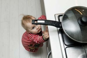 frying-pan-with-handle-sticking-out-with-toddler-below
