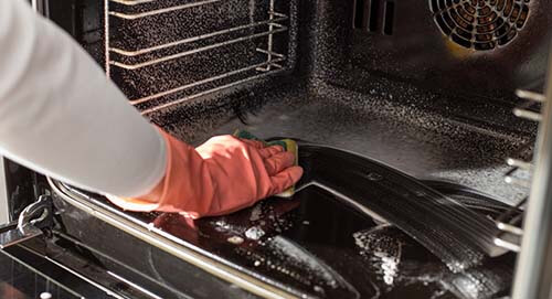 hand-cleaning-inside-of-oven